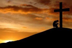 man praying at the cross