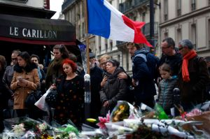 "People gather in front of Le Carillon cafe, a site of the recent attacks, in Paris, Monday Nov. 16, 2015. French President Francois Hollande says the Paris attacks targeted ""youth in all its diversity"" and that the victims were of 19 different nationalities. (AP Photo/Jerome Delay)"