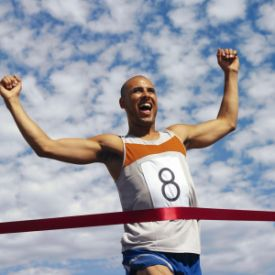 Man Running Reaching Finish Line --- Image by © Royalty-Free/Corbis