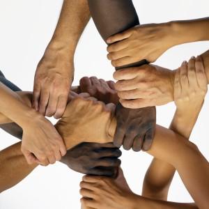 Men and women interlocking hands, close-up, overhead view